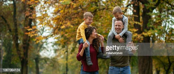 family having fun in park - four people stock pictures, royalty-free photos & images