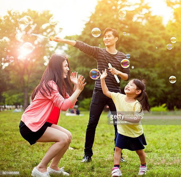 Famille de s'amuser avec des bulles de savon dans le parc