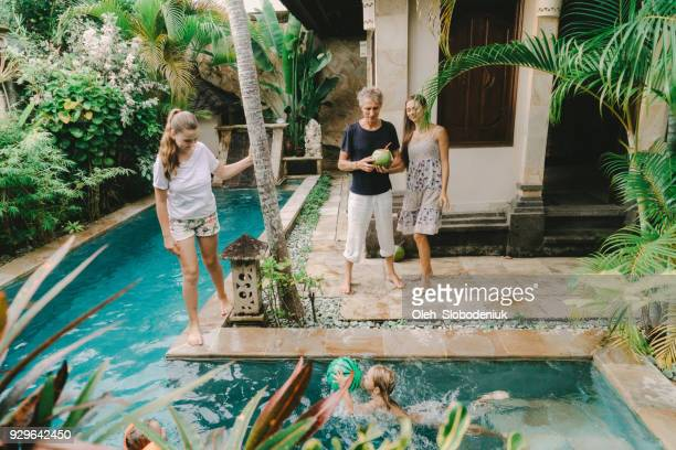 family having fun near   swimming pool - expatriate stock pictures, royalty-free photos & images