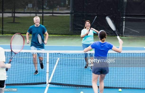 family having fun on tennis court - doubles stock pictures, royalty-free photos & images