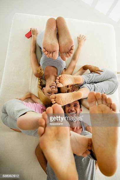 Family having fun on the bed, lifting legs