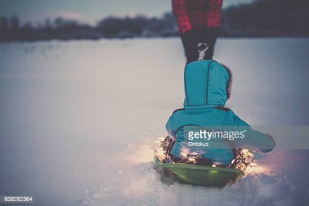 Family having fun Outdoor in winter Illuminated Sled Toboggan