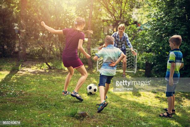 family having fun playing soccer in the garden - sporting term stock pictures, royalty-free photos & images