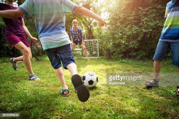 family having fun playing soccer in the garden - termine sportivo foto e immagini stock