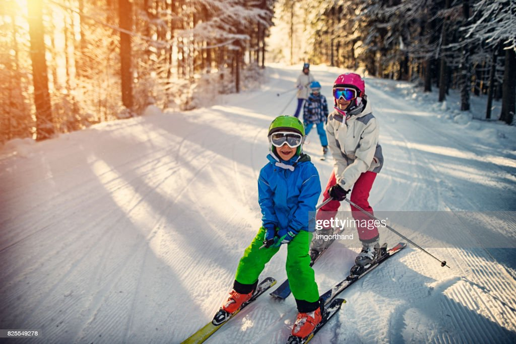 Family having fun skiing together on winter day : Stock Photo
