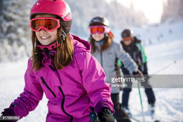 family having fun skiing together - ski stock pictures, royalty-free photos & images