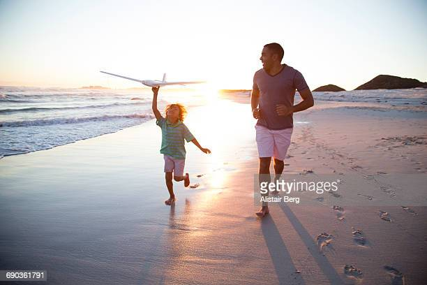 family having fun together on the beach - candid beach stock photos and pictures