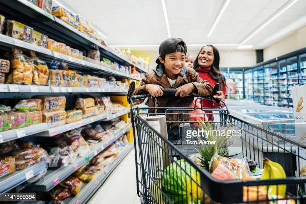 family having fun while out buying groceries. - groceries stock pictures, royalty-free photos & images
