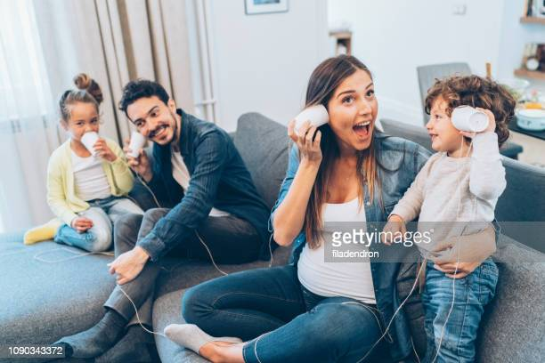 family having fun with string phones - leisure games stock pictures, royalty-free photos & images