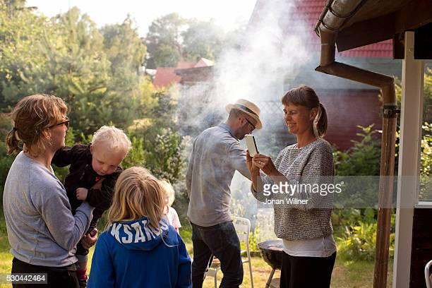 Family having grill in garden, Ystad, Skane, Sweden