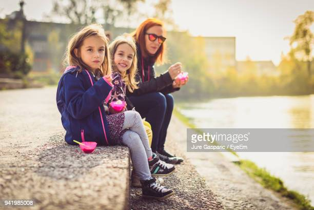 Family Having Ice Cream While Sitting At Riverbank