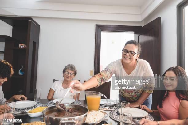 family having lunch at dining table served with feijoada, typical brazilian black bean stew - feijoada imagens e fotografias de stock