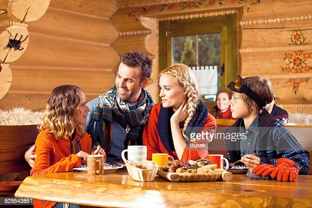 Family having lunch in restaurant after skiing