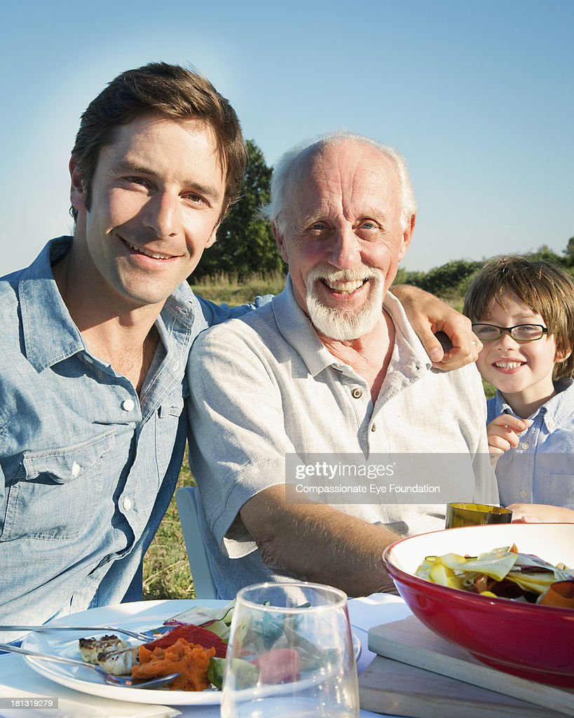 Family having lunch outdoors : Stock Photo