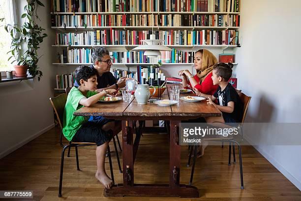 family having meal at table by bookshelf - eettafel stockfoto's en -beelden