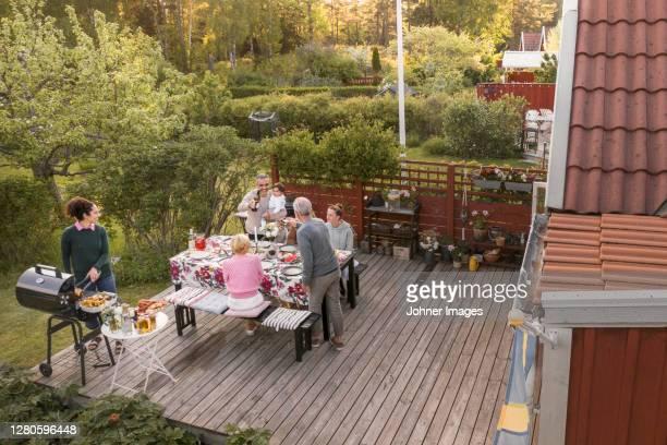 family having meal in garden - コテージ ストックフォトと画像