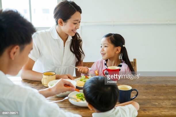 family having meals at table - 食卓 ストックフォトと画像