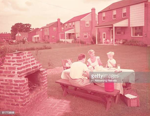 Family having picnic and grill in backyard. (Photo by H. Armstrong Roberts/Retrofile/Getty Images)