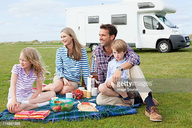 Family having picnic by caravan