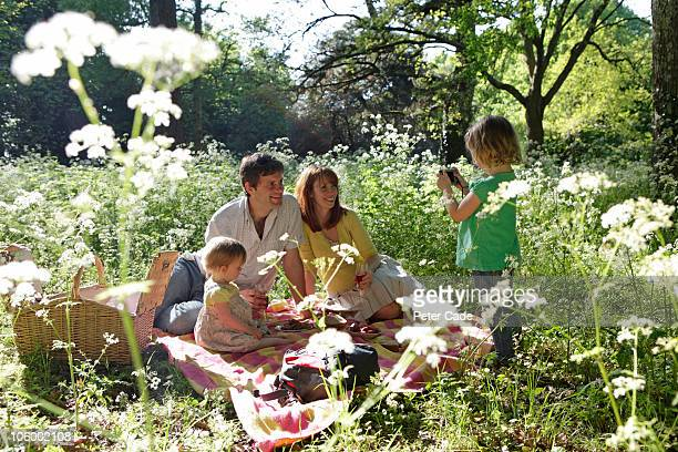 family having picnic, child taking photo