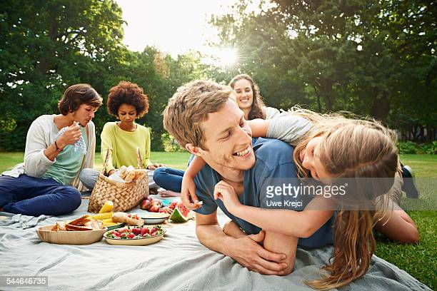 family having picnic in park - picknick stock-fotos und bilder