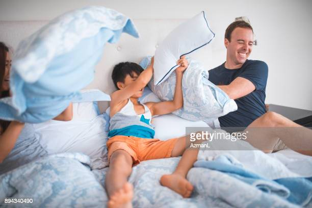 Family having pillow fight in the bed
