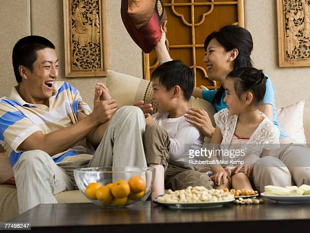 Family having pillow fight on sofa laughing