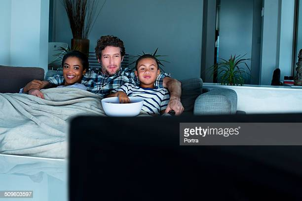 family having popcorn while watching tv - family watching tv stock pictures, royalty-free photos & images