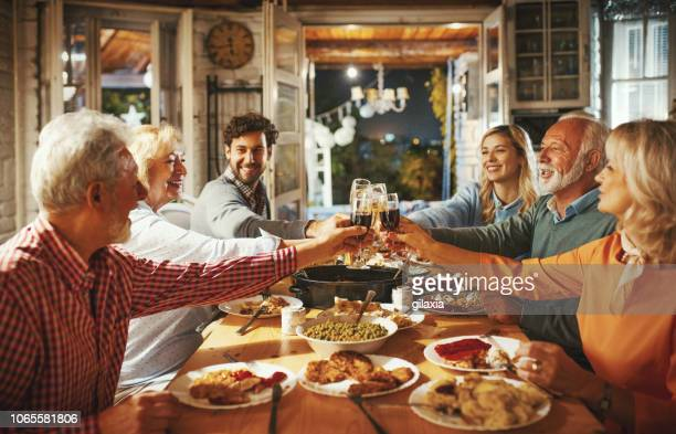 family having thanksgiving dinner. - thanksgiving holiday stock pictures, royalty-free photos & images