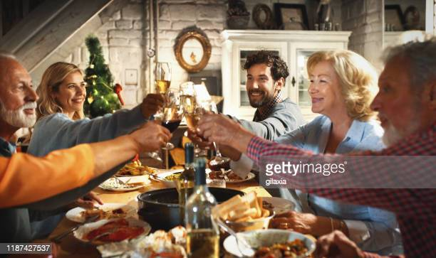 family having thanksgiving dinner. - evening meal stock pictures, royalty-free photos & images