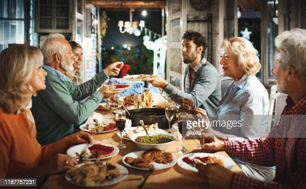 family having thanksgiving dinner. - christmas family stock pictures, royalty-free photos & images