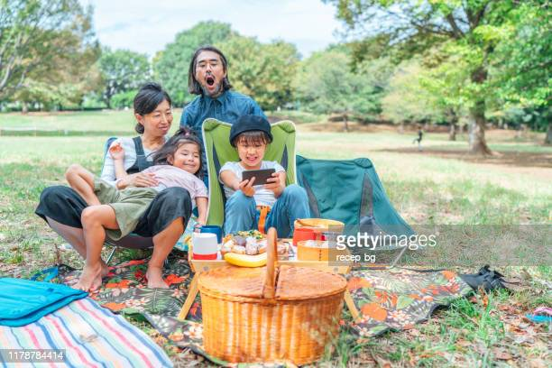 公共の公園でビーガンピクニックを持ち、自分撮りをする家族 - ピクニック ストックフォトと画像