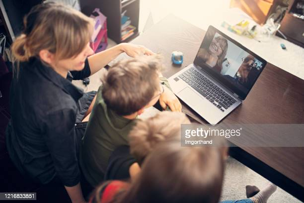 family having video chat with grandparents - lockdown stock pictures, royalty-free photos & images