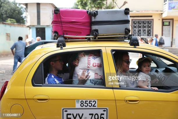 A family heading to Medellin Colombia sit in a taxi after crossing near the Simón Bolívar international bridge which connects Cúcuta with the...
