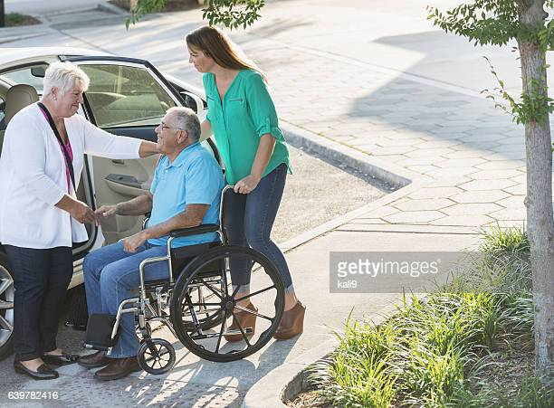 Family helping senior man from car to wheelchair