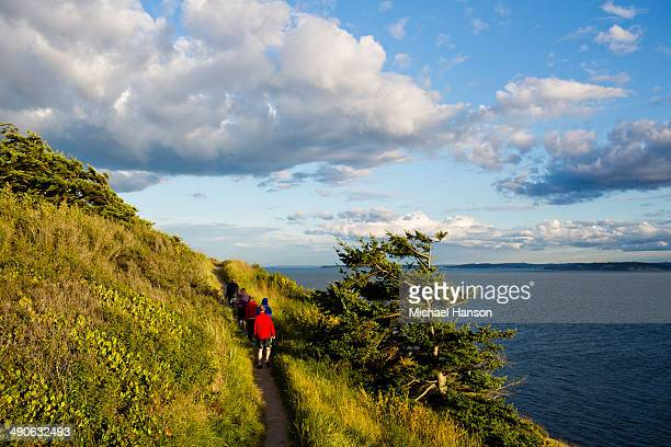 a family hikes along a trail while enjoying the views off the coast of whidbey island from ebey state park. - puget sound stock pictures, royalty-free photos & images