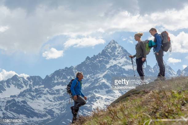 family hikes along mountain ridge in the morning - top garment stock pictures, royalty-free photos & images