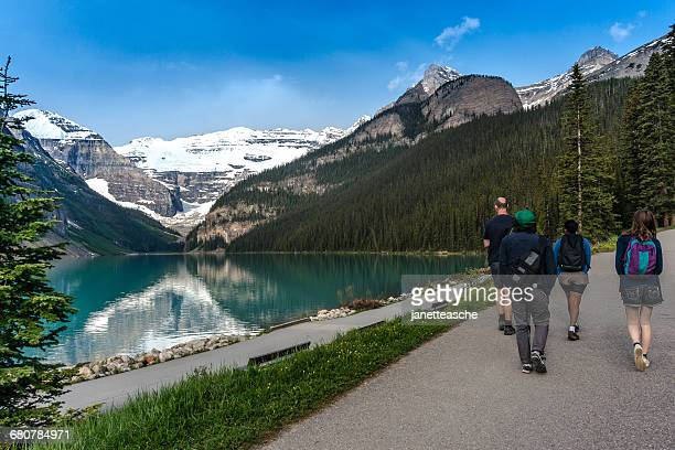 family hiking by lake louise, banff national park, canadian rockies, alberta, canada - lake louise lake stock photos and pictures