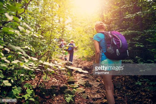 Family hiking in a sunny, green forest