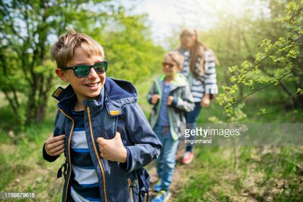 family hiking in spring forest - springtime stock pictures, royalty-free photos & images
