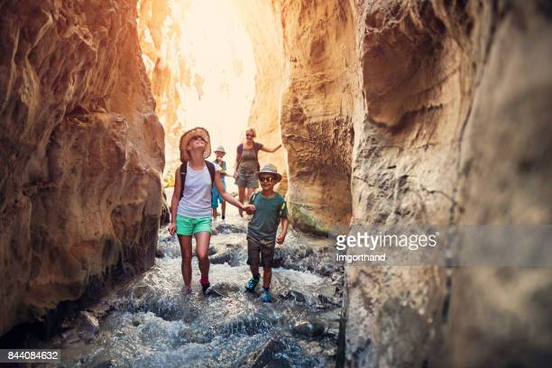 family hiking through rivier in andalusia, spain - canyon foto e immagini stock