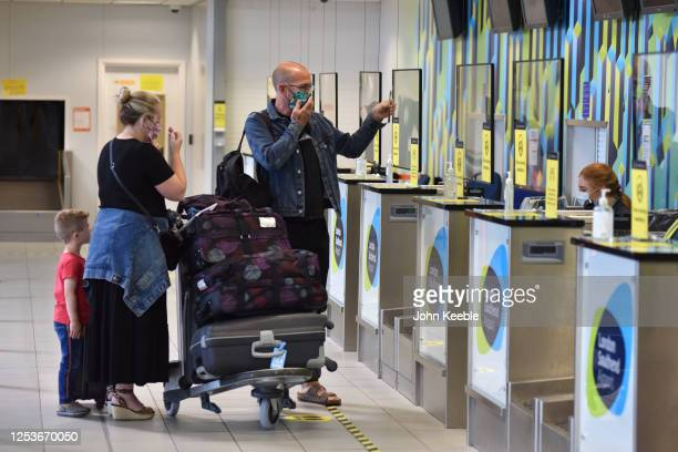 Family hold up information as they check in their bags at the bag drop for Ryanair flight FR2190 to Malaga at London Southend Airport on July 1, 2020...