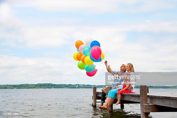 Family holding balloons on wooden pier