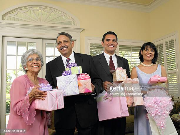 Family holding gifts at quinceanera ceremony, smiling