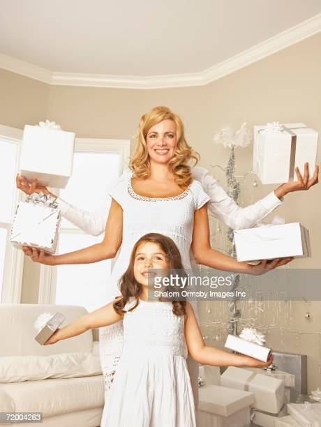 Family holding gifts in outstretched arms on Christmas