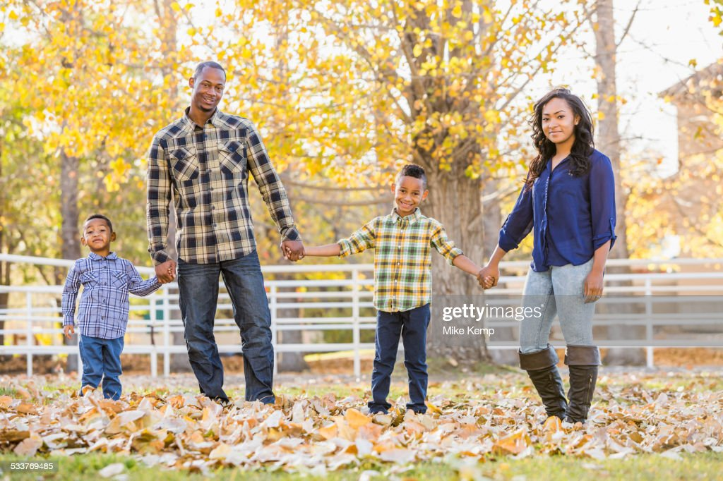 Family holding hands in autumn leaves : Foto stock