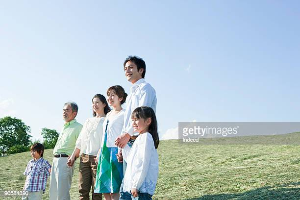 Family holding hands in field, smiling