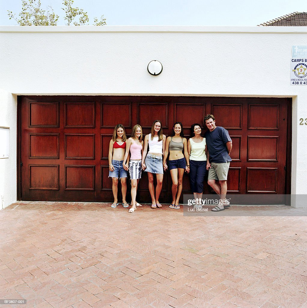 Family Holding Hands In Front Of Garage Doors Portrait Stock Photo