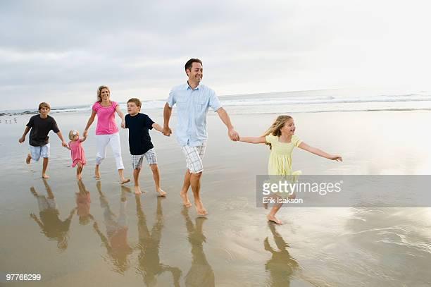 Family holding hands in ocean