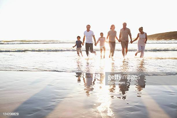family holding hands in water at beach - 6 7 years photos stock photos and pictures